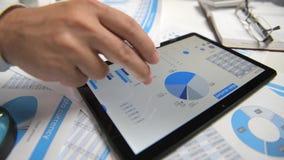 Der arbeitende und berechnende Geschäftsmann, liest und schreibt Berichte Unter Verwendung des Tablette PC Büroangestellter, Tabe stock video