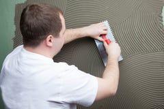 Der Arbeitserbauer trägt Kleber auf einer Wand für einen Keramikziegel auf Stockfotos