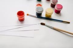 Der Arbeitsplatz des Künstlers für das Zeichnen: Aquarell, Farben, Bürste, Sketchbook, Weißbuch lokalisiert auf Hintergrundtabell Lizenzfreies Stockfoto