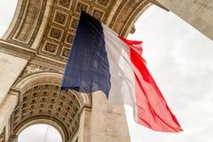 Der Arc de Triomphe mit französischer Flagge stockfoto