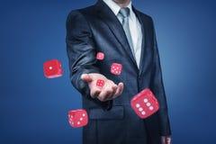 Der Arm eines Geschäftsmannes, der viele roten Kasinowürfel zur Front in einer nahen Ansicht wirft lizenzfreies stockfoto