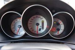 Der Armaturenbrett des Autos glüht orange und mit einem Geschwindigkeitsmesser, Tachometer und anderen Werkzeugen rot, um die Zu stockbilder