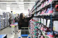 Der asiatische Chinese, der Sportschuhe wählt, Sport beschuht Bereich im Zehnkampfspeicher Lizenzfreie Stockfotografie