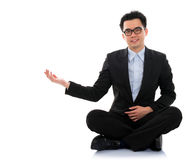 Der asiatische Geschäftsmann, der Leerstelle zeigt, sitzen auf Boden Stockfoto