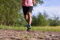 Der asiatische Mann, der auf Waldweg während des Sonnenuntergangs läuft, schließen herauf Beine und Füße stockfoto