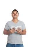 Der asiatische Mann, der ein Buch oben schaut liest, stellen sich vor Lizenzfreie Stockfotografie