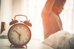 Der asiatische Mann, der heraus nach ausdehnt, wachte mit dem Wecker auf, der sechs O-Uhr zeigt Lizenzfreie Stockfotografie