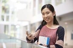 Der asiatische weibliche erwachsene Student, der Telefon verwendet, schaut zur Kamera lizenzfreies stockbild