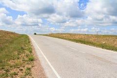 Der Asphaltstraßenlauf diagonal über dem Horizont stockbilder