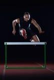 Der Athlet über Hürden springend stockbilder