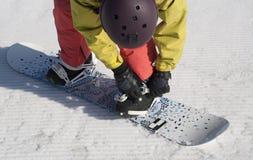 Der Athlet überprüft Befestigungen auf einem Snowboard vor Abfall Lizenzfreies Stockbild