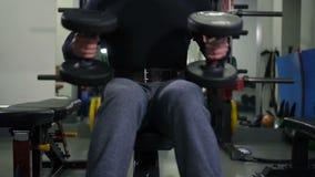 Der Athlet mit Dummköpfen sitzt auf einer Bank, tut eine Übung für zwei Hände 4K langsames MO stock footage