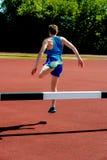 Der Athlet springend über die Hürde Stockfotografie