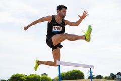 Der Athlet springend über die Hürde Lizenzfreie Stockfotografie