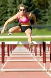 Der Athlet springend über Hürden auf einer Spur Lizenzfreie Stockfotografie