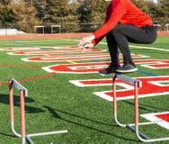 Der Athlet springend über Hürden auf Rasenfeld von der Seite stockfoto