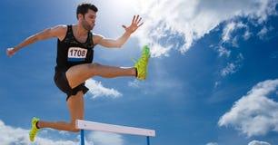 Der Athlet springend über Hürden gegen Himmel im Hintergrund stockfoto