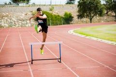 Der Athlet springend über die Hürde Lizenzfreie Stockbilder