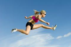 Der Athlet springend gegen einen Himmel-Hintergrund Stockfotos