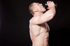 Der Athletenbodybuilder trinkt Wasser aus einem Schüttel-Apparat heraus Lizenzfreies Stockfoto