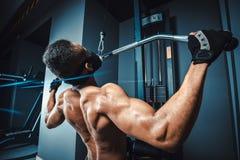 Der athletische Mann des Afroamerikaners, der Übung ziehen tut herein, hintere Ansicht der Maschine herunter schwarzer Eignungsma Lizenzfreie Stockfotos