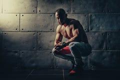 Der athletische Mann des starken Bodybuilders, der oben pumpt, mischt Training bodyb mit Stockfotografie
