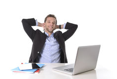 Der attraktive Geschäftsmann, der am Arbeitslächeln glücklich ist, entspannte sich am Computertisch Stockfotografie