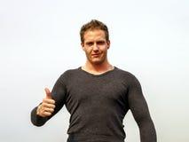 Der attraktive junge Modemann, der die Daumen zeigt, up Geste Lizenzfreie Stockbilder