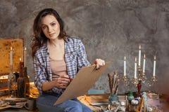 Der attraktive Künstler, den der Lehrer im Verlauf der Zeichnung an den Studenten vorwärts betrachtet Sie zeichnet Öl und Acryl Stockfotografie