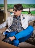 Der attraktive Mann, der im Innenraum aufwirft, kleidete zufällige tragende Sonnenbrille Lizenzfreie Stockfotos