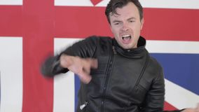Der attraktive Mann, der in der schwarzen ledernen Motorradjacke gekleidet wird, singt und tanzt stock video