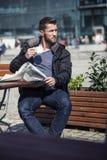 Der attraktive Mann sitzt in einer Kaffeestube das Nachrichtenpapier lesend Stockfotografie