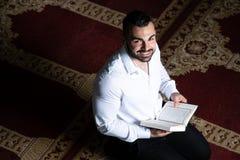 Der attraktive moslemische Guy Is Listen On Headset-Koran stockfoto