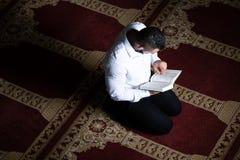 Der attraktive moslemische Guy Is Listen On Headset-Koran stockfotografie