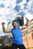 Der attraktive Sportmann, der Sieg tun und der Sieger unterzeichnen mit seinen Armen nach laufendem Training im städtischen Gesch Stockfotos