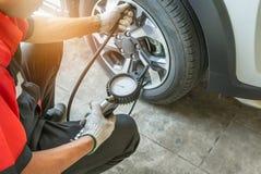 Der aufblasende Mechaniker setzte Luft in den Reifen und in die Prüfung des Luftdrucks mit Manometerdruck lizenzfreie stockfotografie