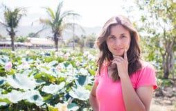 Der Aufenthalt des jungen Mädchens im Lotosteich und -lächeln Lizenzfreies Stockfoto