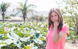 Der Aufenthalt des jungen Mädchens im Lotosteich und -lächeln Lizenzfreie Stockfotografie