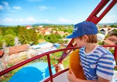 Der aufgeregte Junge, der die Ansicht von genießt, Riesenrad herein Vergnügungspark Stockbild