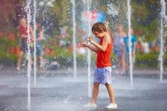 Der aufgeregte Junge, der Spaß zwischen Wasser hat, spritzt, im Brunnen Sommer in der Stadt Stockfoto