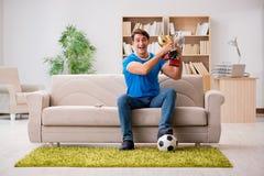 Der aufpassende Fußball des Mannes zu Hause stockfotos