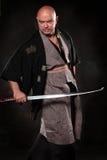 Der Ausdruckmann im Bild eines Samurais mit Klinge in der Hand Stockfotos