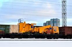 Der auseinandergebaute gelbe Bergbau-LKW, der auf eine Bahnplattform geladen wird, kostet Eisenbahnlinien stockbilder