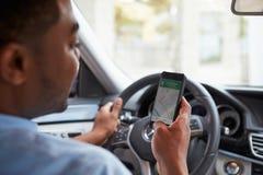 In der Autoansicht des jungen männlichen Afroamerikaners, der Karten-APP an seinem Telefon betrachtet Stockfoto