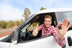 Der Autofahrer, der Autoschlüssel zeigen und die Daumen up glückliches Stockfotos