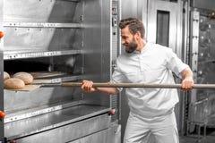Der Bäcker, der heraus vom Ofen nimmt, backte buckweat Brot stockfoto