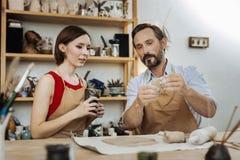 Der bärtige Mann, der über die Herstellung der Töpferware spricht, höhlt seinen Freund lizenzfreie stockfotos