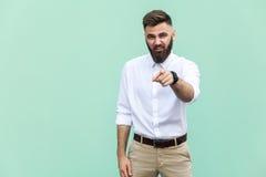 Der bärtige Mann, der Finger auf Kamera und Gespött über jemand zeigt Stockfotos