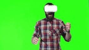 Der bärtige Mann, der VR trägt, googelt auf grünem Schirm stock video footage