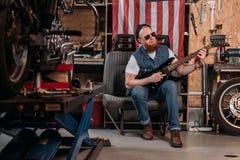 der bärtige Mann, der E-Gitarre an der Garage mit USA spielt, kennzeichnen das Hängen Stockfotografie